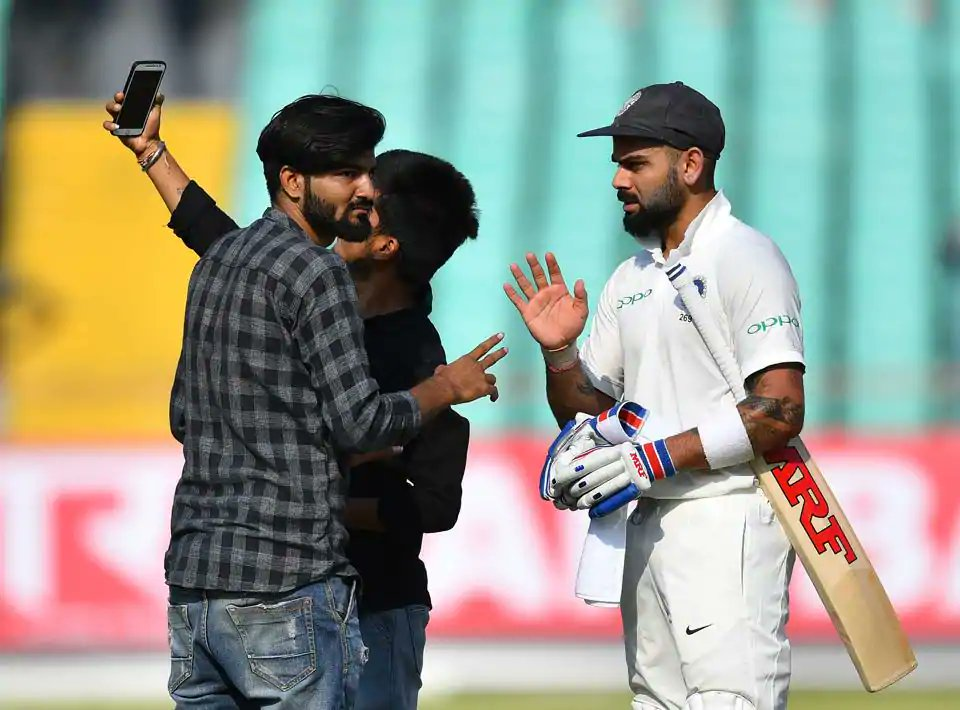 Virat Kohli with the fans who breached security at Rajkot | AFP