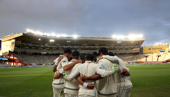 New Zealand players in a team huddle in a day-night test match against England | MICHAEL BRADLEY/AFP/Getty Images