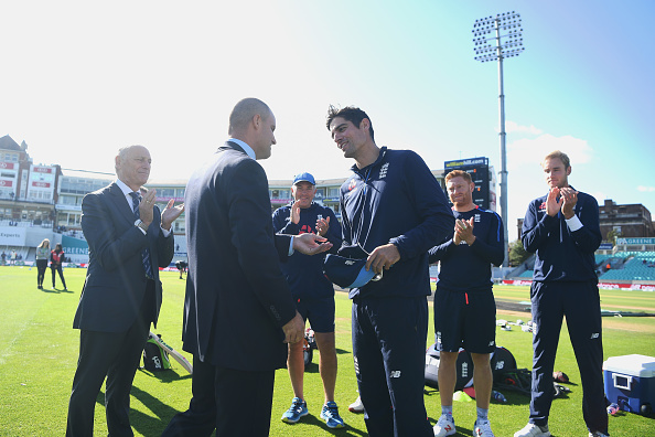Alastair Cook receives a special cap from Andrew Strauss before his last Test | Getty