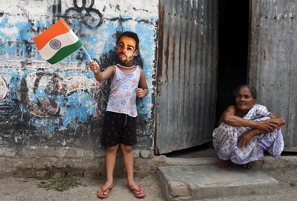An Indian cricket fan wears a mask of the face of India's captain Virat Kohli | GETTY